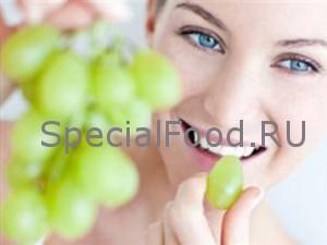 Женщина кушает виноград