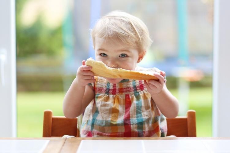 Ребенок кушает сливочное масло